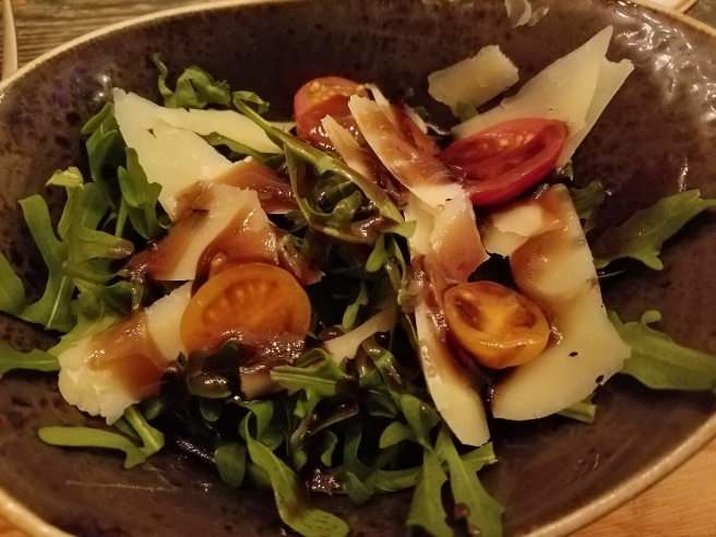 House arugula salad with shaved aged provolone, grape tomatoes, and a sweet balsamic glaze dressing